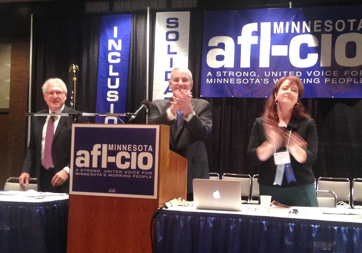 Governor Mark Dayton acknowledged the applause of union members at the Minnesota AFL-CIO convention. With him are federation President Bill McCarthy and Secretary-Treasurer Julie Blaha. Workday Minnesota photo