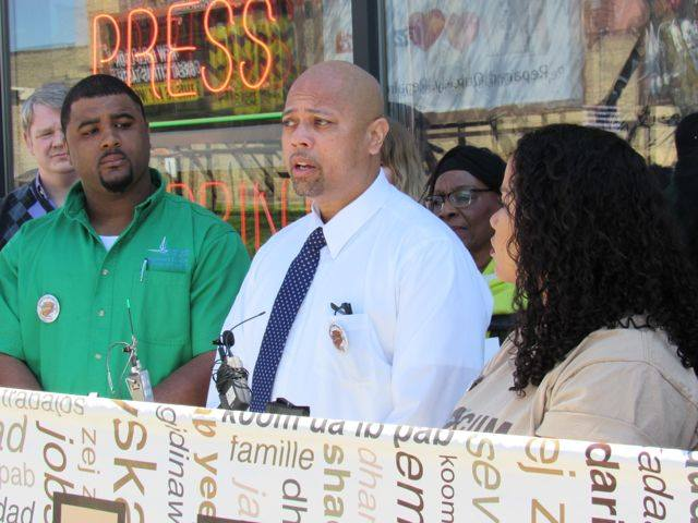 """Frank Brown (center), owner of Minuteman Press at 2101 Hennepin Ave. So. in Minneapolis: """"Making Minneapolis work better for people of color is a priority for everyone."""" He said the lack of paid sick days represents """"a moral crisis facing our city."""" Photo by Steve Share, Minneapolis Labor Review"""