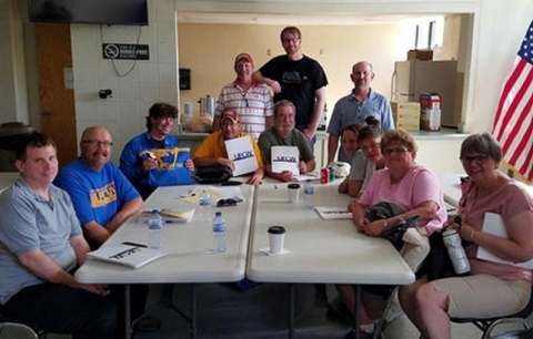 "Members of the Local 1189 bargaining committee celebrated their tentative deal with northern grocers – negotiated in a dimly lit basement at the Labor Temple after storms knocked out power in the Duluth area. ""Unable to print or make copies of the new offer, the groups met and documented the improvements the old fashioned way – in writing,"" the union said. Photo courtesy of UFCW Local 1189."
